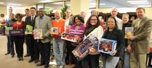 Bobby Cagle, DFCS Director, Parole Board Member James Donald and Executive Director of Parole Michael Nail pose with their donated gifts with parole staff.
